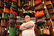 A merchant of leather goods, San Lorenzo market, Florence, Italy.