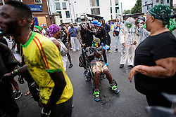 © Licensed to London News Pictures. 28/08/2016. London, UK. Revellers covered in oil enjoy Jouvert, a paint fight that officially marks the start of the Notting Hill carnival. The two day event is the second largest street festival in the world after the Rio Carnival in Brazil, attracting over 1 million people to the streets of West London. Photo credit: Ben Cawthra/LNP