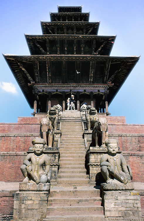 Frontal view of Nyatapola temple in Bhaktapur, Nepal.  Viewpoint looking up its steep staircase.  Built in 1708.   Seated statue of Shiva in the foreground.  All five levels of its pagoda-like roof are visible against the sky.
