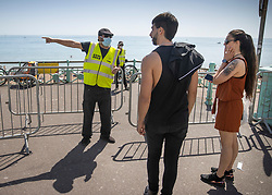 © Licensed to London News Pictures. 25/05/2020. Brighton, UK. A steward directs people away from the beach due to overcrowding at Brighton as the Bank Holiday weather brings high temperatures and sunshine. The government has announced a series of measures to slowly ease lockdown, which was introduced to fight the spread of the COVID-19 strain of coronavirus. Photo credit: Peter Macdiarmid/LNP