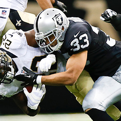 Aug 16, 2013; New Orleans, LA, USA; Oakland Raiders strong safety Tyvon Branch (33) tackles New Orleans Saints running back Mark Ingram (22) during the second quarter of a preseason game at the Mercedes-Benz Superdome. Mandatory Credit: Derick E. Hingle-USA TODAY Sports