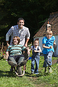 Father and children (5-9) racing with wheelbarrow outside cottage