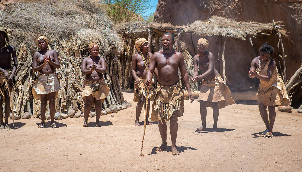 Damaran peoples stand and sing in a line at the Damara Living Museum, located in Twyfelfontein, near Namibia, Africa.