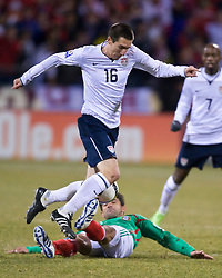 United States midfielder Sacha Kljestan (16) is tripped up by Mexico midfielder Antonio Naelson (15).  The United States men's soccer team defeated the Mexican national team 2-0 in CONCACAF final group qualifying for the 2010 World Cup at Columbus Crew Stadium in Columbus, Ohio on February 11, 2009.