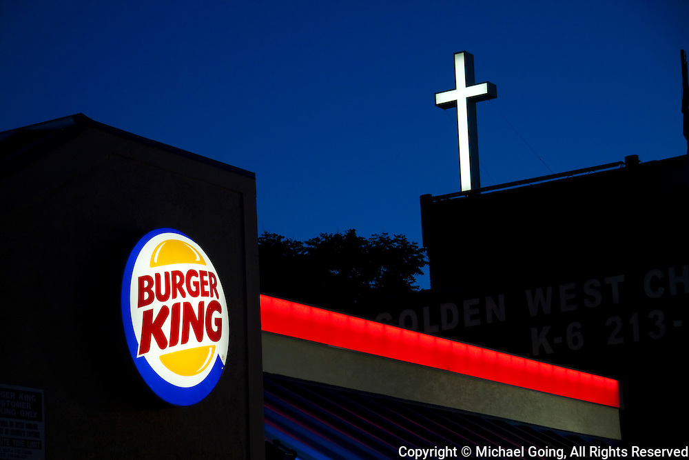 Twilight photo of Burger King fast food restaurant with church cross in background