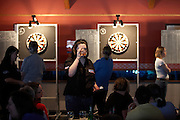 A large, manly woman sips a pint of lager during a darts tournament where she competes in an England Open tournament.
