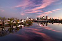 Dramatic view of the Minneapolis skyline and reflections at dusk over the Mississippi river in Minnesota, USA.