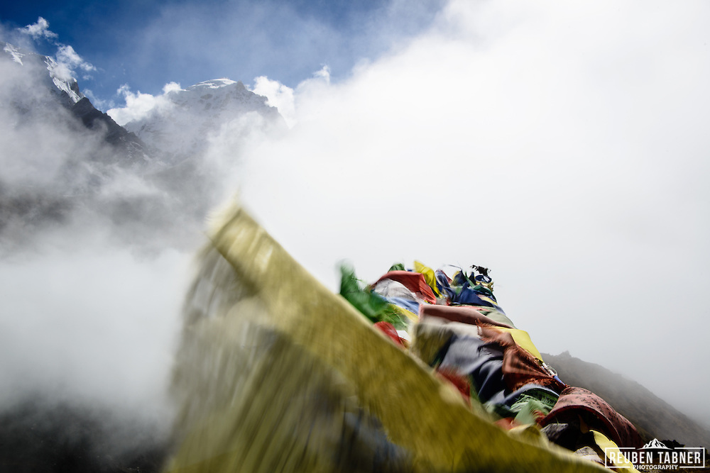 Preyer flags flutter in the wind as cloud fills the valley below, above the village of Machermo in the Sagarmatha National Park, Nepal.