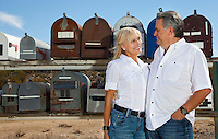 Senior couple stand in front of rural mailboxes