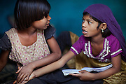 Poonam, 10, (right) and her older sister Jyoti, 11, are having an argument while completing some homework on the floor inside their newly built home in Oriya Basti, one of the water-contaminated colonies in Bhopal, central India, near the abandoned Union Carbide (now DOW Chemical) industrial complex, site of the infamous '1984 Gas Disaster'.