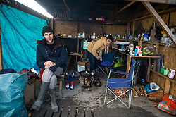 © Licensed to London News Pictures. 23/01/2016. Dunkirk, France. Two young migrants pose for a photograph inside their makeshift shop in the Dunkirk camp. Labour Party leader JEREMY CORBYN visited the camp known as the 'Jungle' in Calais, France, where thousands of migrants and refugees attempting to reach the UK are currently living. Photo credit: Ben Cawthra/LNP