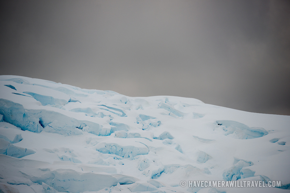 Deep crevasses in a glacier along the Lemaire Channel on the Antarctic Peninsula stand out against gray overcast skies.