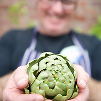 Chef Steve Cumper holds an in-season artichoke at his restaurant, the Red Velvet Lounge, Cygnet, Tasmania