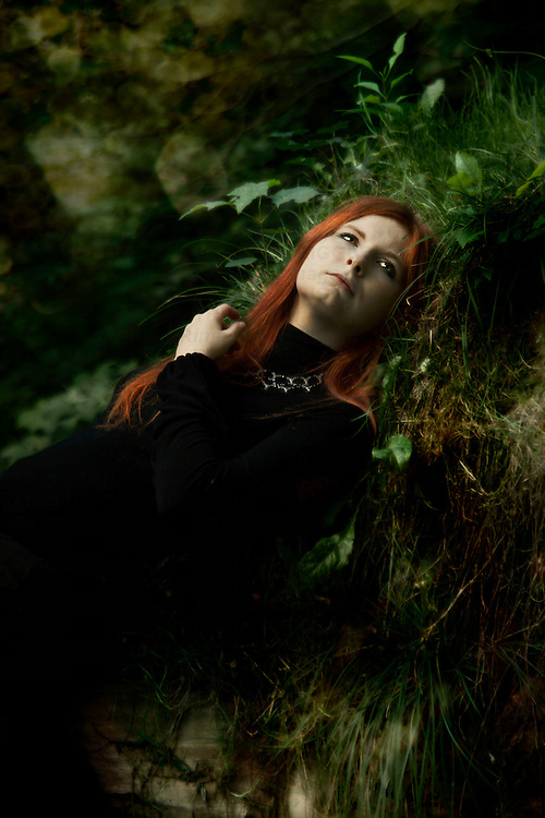 A red haired lady in a black dress, lying on the grass in the forest with sad stare emotion