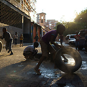"""Children play with old car tyres on a quiet street in Hillbrow, an inner-city neighbourhood in Johannesburg, South Africa with a reputation for drugs, violence and crime. The children fill the tyres with gravel and sand, which makes a sound as they roll them and produces """"engine smoke""""."""