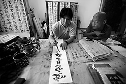 Chinese disabled artist Xi Fu (L) observes his calligraphy teacher Liu Shenwei during a practice session in Daxing Arts Centre on the outskirts of Beijing, China 18 June 2013. At the age of 18, he joined a children's art class at an art centre and began to learn painting from art teacher Ren Zhijun, who was so taken by Xi Fu that he taught him for free. Another two teachers noticed his talent and started teaching him calligraphy. Xi Fu practiced for hours everyday even though his condition made it painful for him to remain in his writing position for long periods of time. It was however only three years later in 2003 that his teachers proclaim him good enough to make a living from his art. Xi Fu's story is one that tells of how strong determination and hard work overcame the difficulties of surviving in a society scant with infrastructure and support for the disabled and where they are often discriminated and sidelined.