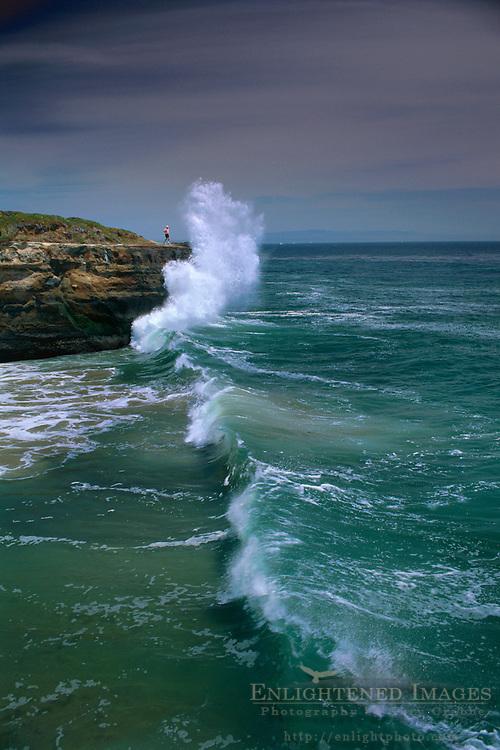 Wave crashing on coastal bluff next to person on West Cliff Drive, Santa Cruz, California