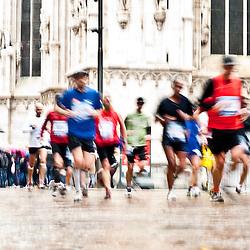 Milan, April 15, 2012: Milan City Marathon runners pass by Duomo cathedral in a rainy day. Milano, 15 Aprile 2012: Milano city marathon, maratoneti corrono a fianco della cattedrale del Duomo di Milano in una giornata di pioggia. durante la maratona di Milano