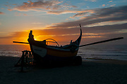 Silhouette of traditional colorful Portuguese fishing boat on the beach at Vieira de Leiria. A Portuguese village and also a parish in the municipality of Marinha Grande, Portugal at sunset
