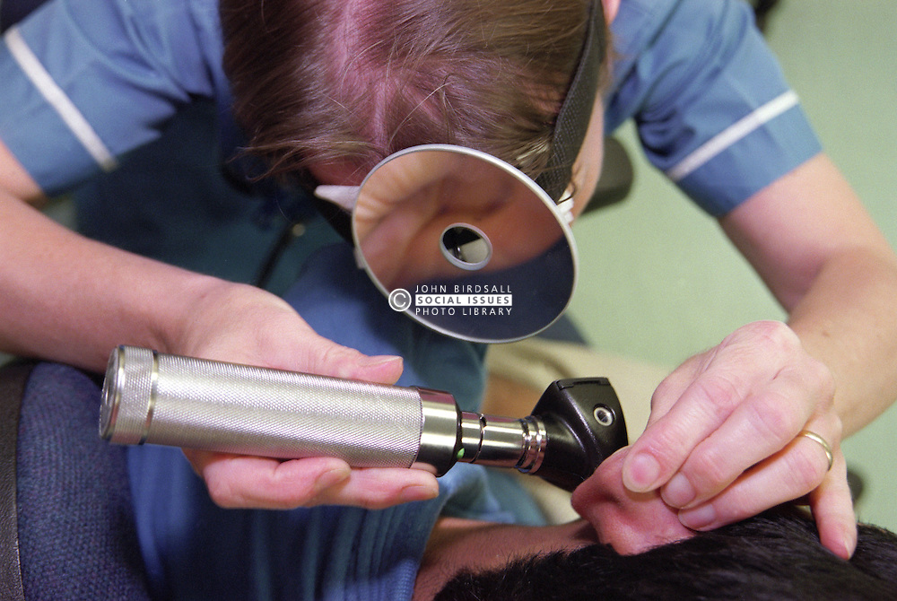 Staff nurse in aural care centre examining patient's ear canal using head mirror and otoscope,