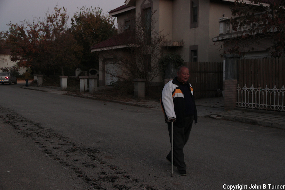 A local on his evening walk two days before the first snowfall. The line of holes in the road will soon be dug up to provide new gaslines to the villas.