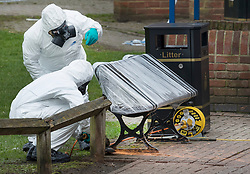 © Licensed to London News Pictures. 23/03/2018. Salisbury, UK. Police in protective suits and gas masks use an angle grinder to remove the bench where former Russian spy Sergei Skripal and his daughter Yulia were poisoned with nerve agent in Salisbury. The couple where found unconscious the bench in Salisbury shopping centre on 4th March 2018. Photo credit: Peter Macdiarmid/LNP