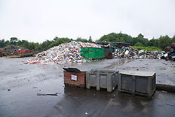 Loose tin plate scrap piled up at scrap metal recycling centre waiting to be sorted and processed,