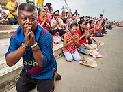 "23 JUNE 2015 - MAHACHAI, SAMUT SAKHON, THAILAND: People pray as the City Pillar Shrine is brought to a waiting fishing boat in Mahachai. The Chaopho Lak Mueang Procession (City Pillar Shrine Procession) is a religious festival that takes place in June in front of city hall in Mahachai. The ""Chaopho Lak Mueang"" is  placed on a fishing boat and taken across the Tha Chin River from Talat Maha Chai to Tha Chalom in the area of Wat Suwannaram and then paraded through the community before returning to the temple in Mahachai.   PHOTO BY JACK KURTZ"