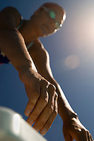 Female swimmer on starting blocks focus on hands (low angle view)