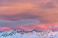 Spectacular colored sky over the group of the Bergüner Stöcke with the peaks Piz Mitgel, Corn da Tinizong and Piz Ela, Parc Ela at dusk, Grisons, Switzerland