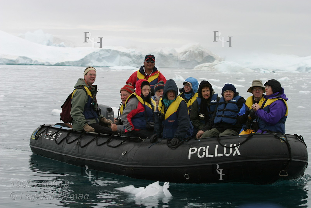 Cruise ship passengers in rubber Zodiac raft explore field of massive icebergs at Ilulissat Kangerlua Icefjord in Disko Bay, Greenland.