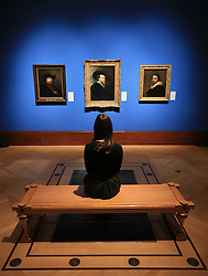 An employee of the Royal Collection Trust looks at (left to right) Rembrandt's Self-Portrait in a Flat Cap, Rubens' A Self-Portrait, and Myens' A Self-Portrait, which are on display in the Portrait of the Artist exhibition at the Queen's Gallery, Buckingham Palace, London.