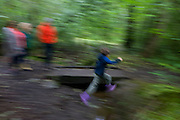 A young boy leaps across a small stream in woods south of Sheffield, England UK.