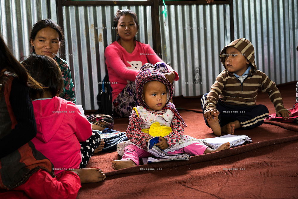 Lactating mothers sit by the side as their young children play and learn in the SOS Children's Villages Child Care Space in Rayale, Nepal on 1 July 2015. The Child Care Space was set up by SOS Children's Villages soon after the earthquake so that they children of the village can come together to play, learn, and get over the trauma of the disaster, while their parents can be free to reconstruct their homes and go off to get rations and relief kits. Photo by Suzanne Lee for SOS Children's Villages