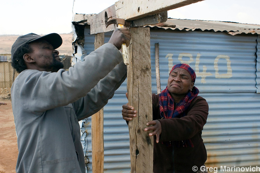 Sarafina Mokoena and neiughbour Barend Ntsoe work on an addition to her and her husband's shackk in Boiketlong squatter camp. They are extending to make room for a new child. Residents of the informal settlements that dot the Sebokeng/Evation area south of Johannesburg have been taking to the streets to protest lack of service delivery, or inadequate services that are not what they believe were promised them by the African National Congress before they came into power in 1994. August 26, 2007. Photo Greg Marinovich