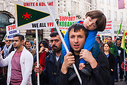 London, October 19th 2014. Hundreds of London's Kurdish community march throgh the capital in protest against ISIS and the Turkish government who they accuse, by not getting involved in military action against ISIS, of using the Jihadists to wipe out Kurds who have long been campaigning for an independent Kurdistan. PICTURED: A child sleeps as his father marches.