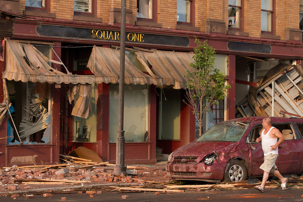 An onlookers runs past storm damage on Main St in downtown Springfield, MA where a tornado struck on Wednesday afternoon June 1, 2011.  (Matthew Cavanaugh for The Boston Globe)