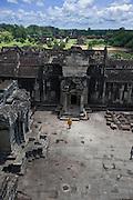 A monk makes his way through the courtyard at Angkor Wat.