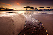 Colourful sunset reflected on wet beach, pools and the sea itself, at the coast at Rhosneigr, West Anglesey, Wales