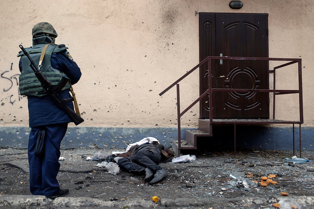 A soldier watches over the body of a civilian who was killed by shelling on Marata Street on February 10, 2015 in Kramatorsk, Donetsk Oblast, Ukraine.