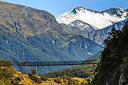 Tourists pause for a rest on a suspension bridge on the Rob Roy Glacier Trek near Wanaka, South Island, New Zealand