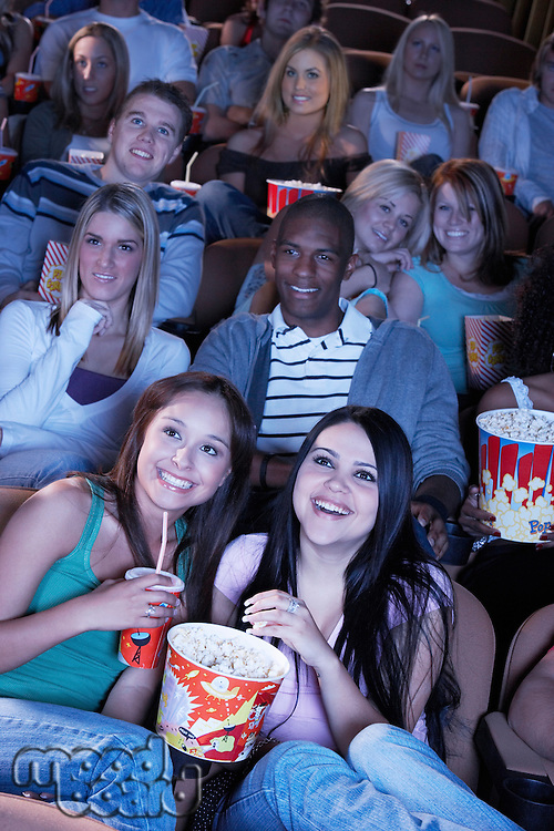 Young women sharing popcorn Watching Movie Together
