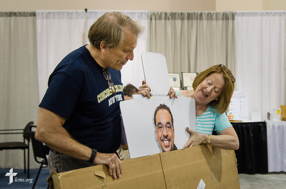 Jim Bunn and Kathy Dresser from Concordia College–New York prepare their exhibit on Friday, July 8, 2016, before the start of the 66th Regular Convention of The Lutheran Church–Missouri Synod at the Wisconsin Center in Milwaukee. LCMS Communications/Frank Kohn