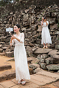 A Chinese women take a selfie photo from her phone dressed in white bridal dresses standing by the ancient ruins of Angkor Thom, Siem Reap Province, Cambodia, South East Asia. A second woman, also dressed as a bride, stands on the stone wall with a DSLR camera.  (photo by Andrew Aitchison / In pictures via Getty Images)(photo by Andrew Aitchison / In pictures via Getty Images)
