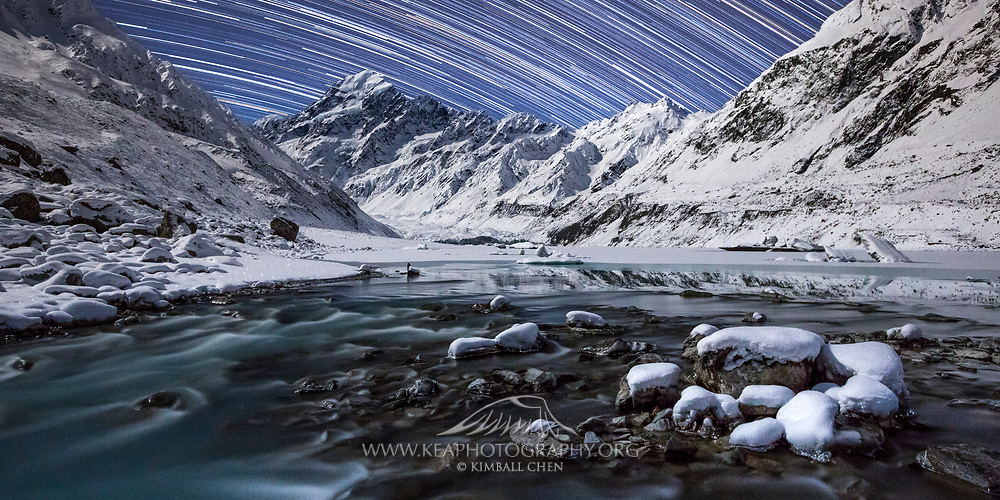 A wide print of star trails over a stunningly clear but cold winter night on the partially frozen Hooker Lake, looking out at New Zealand's highest point, Mount Cook.
