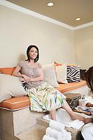 Portrait of a happy woman getting pedicure in beauty spa