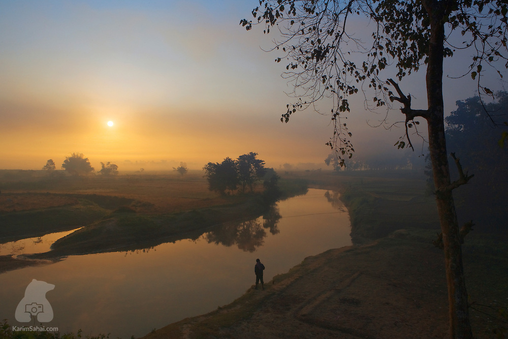 Man by a river at sunrise, Jorhat, Assam, India.