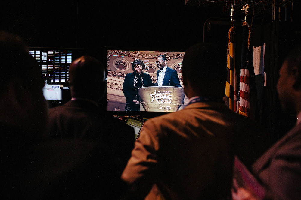 Dr. Ben Carson's staff watch from backstage while he and his wife, Candy, take the podium during the final day of the Conservative Political Action Conference (CPAC) at the Gaylord National Resort & Convention Center in National Harbor, Md.