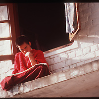 Photo by David Stephenson.  A Tibetan monk studies on a window ledge in Dharamsala, India, in 11/91.