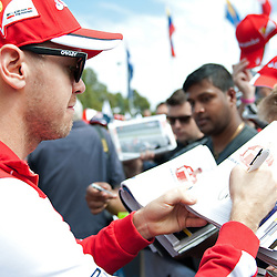 Sebastian Vettel of Scuderia Ferrari signing autographs.<br /> Round 1 - opening day of the 2015 Formula 1 Rolex Australian Grand Prix at The circuit of Albert Park, Melbourne, Victoria on the 12th March 2015.<br /> Wayne Neal | SportPix.org.uk